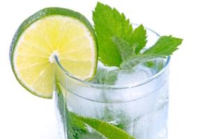 Eiswürfel in einem Glas mit Minze und Limette